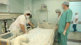 Eine Gruppe Doktoren schließen das Gerät an, um den Patienten nach der Operation zu erhitzen stock video footage