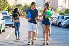 Eine Gruppe Freunde, die in der Straße nach Klasse sprechen Lizenzfreie Stockbilder