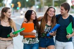 Eine Gruppe Freunde, die in der Straße nach Klasse sprechen Lizenzfreie Stockfotografie