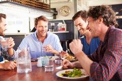 Eine Gruppe Freunde, die in einem Restaurant zu Mittag essen Stockbild