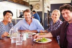 Eine Gruppe Freunde, die in einem Restaurant zu Mittag essen Lizenzfreie Stockbilder