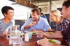 Eine Gruppe Freunde, die in einem Restaurant zu Mittag essen Stockbilder