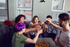 Eine Gruppe Freunde klirrt Gl?ser mit Bier im Raum lizenzfreies stockbild