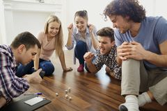Eine Gruppe Freunde spielen Brettspiele auf dem Boden zuhause stockfotos