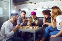 Eine Gruppe Freunde spielen Brettspiele im Raum lizenzfreie stockfotos