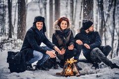Eine Gruppe glückliche Freunde inszenierte ein Kampieren inmitten eines schneebedeckten Waldes stockfotografie