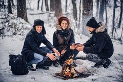 Eine Gruppe glückliche Freunde inszenierte ein Kampieren inmitten eines schneebedeckten Waldes stockbilder