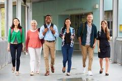 Eine Gruppe glückliche Lehrer, die in einen Schulkorridor gehen Lizenzfreies Stockfoto