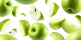 Eine Gruppe grüne Äpfel, die auf einem weißen Hintergrund frei schweben stockbilder