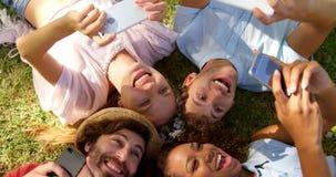 Eine Gruppe Hippie-Freundlügen Kopf-an-Kopf- und Aufpassen ihres Smartphone stock video