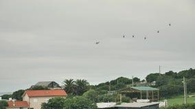 Eine Gruppe Hubschrauber, die über den Himmel der Kleinstadt am bewölkten regnerischen Tag fliegen stock video footage