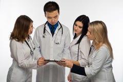 Eine Gruppe junge Doktoren bespricht etwas vor treatme lizenzfreie stockfotos