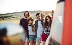 Eine Gruppe junge Freunde auf einem roadtrip durch Landschaft, ein Mehrzweckfahrzeug bereitstehend lizenzfreie stockbilder