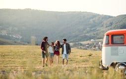 Eine Gruppe junge Freunde auf einem roadtrip durch Landschaft, gehend lizenzfreie stockfotografie