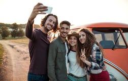 Eine Gruppe junge Freunde auf einem roadtrip durch Landschaft, selfie nehmend lizenzfreie stockbilder