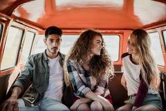 Eine Gruppe junge Freunde auf einem roadtrip durch Landschaft, sitzend in einem Mehrzweckfahrzeug lizenzfreie stockfotografie
