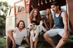Eine Gruppe junge Freunde mit einem Hund auf einem roadtrip durch Landschaft stockfotografie