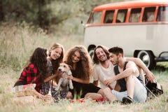 Eine Gruppe junge Freunde mit einem Hund, der auf Gras auf einem roadtrip durch Landschaft sitzt stockfotografie