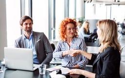 Eine Gruppe junge Geschäftsleute, die in einem Büro, Hände rüttelnd sitzen lizenzfreies stockbild