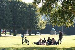 Eine Gruppe junge Leute genießen die europäische Sonne und sitzen auf dem Rasen im Park stockbilder