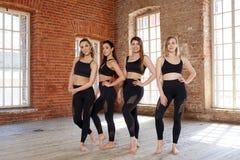 Eine Gruppe junge sportliche Mädchen, die in der Halle für das Tanzen stehen Weibliche Begleiter in der Turnhalle, entspannend na stockbild