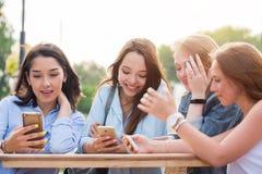 Eine Gruppe junge Studentinnen, die an einem Tisch im Park und mit einem Lächeln etwas besprechend hält Smartphones sitzen Chat,  lizenzfreie stockfotos