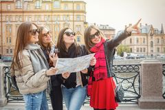 Eine Gruppe junge weibliche Touristen suchen nach Anziehungskräften in einer europäischen Stadt auf der Karte Vier nett und schön stockbild