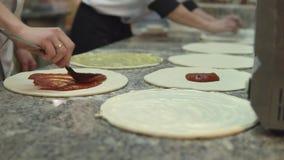 Eine Gruppe Köche setzte gleichmäßig die Soße auf die Kreise des Teigs für die Herstellung der Pizza stock video