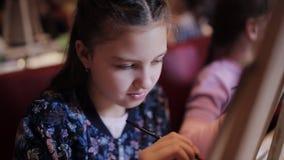 Eine Gruppe Kinder in einem Studio der schöner Kunst mit Farben und Gestellen Kinder schreiben ein Bild auf Segeltuch stock video