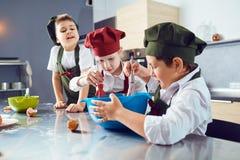 Eine Gruppe Kinder kochen in der Küche stockbilder