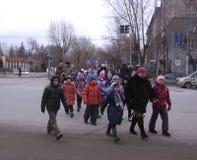 Eine Gruppe Kinder, welche die Straße unter Aufsicht des Prüfers kreuzen lizenzfreie stockfotos