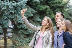Eine Gruppe lächelnde Freunde, die einen Handy nehmen, werden draußen fotografiert lizenzfreie stockfotos