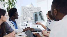 Eine Gruppe multiethnische Berufsdoktoren, die einen Röntgenstrahl der Lungen des Patienten während ihr Sitzen am Tisch herein be stock footage