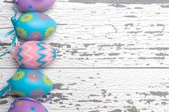 Eine Gruppe Pastell färbte Ostereier auf einem weißen hölzernen Hintergrund Lizenzfreie Stockfotos