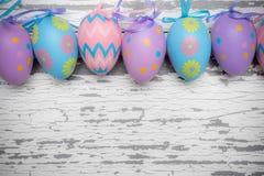 Eine Gruppe Pastell färbte Ostereier auf einem weißen hölzernen Hintergrund Stockfotografie
