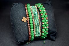 Eine Gruppe perlenbesetzte Armbänder auf einer dunklen Oberfläche Grün- und Goldfarben Stockbilder
