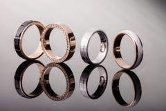 Eine Gruppe Ringe der Verpflichtungsdiamantenen hochzeit auf glattem Hintergrund, Isolat, Nahaufnahme Lizenzfreies Stockbild