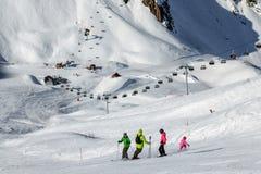 Eine Gruppe Skifahrer, die auf einer Skisteigung in einem Berg-cirque an einem sonnigen Tag auf dem Sesselbahnhintergrund stehen Lizenzfreies Stockfoto