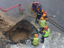 Eine Gruppe Straßenarbeiter von den öffentlichen Einrichtungen in den reflektierenden speziellen Westen besprechen einen Notfall stockbilder