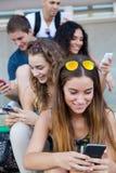 Eine Gruppe Studenten, die Spaß mit Smartphones nach Klasse haben Lizenzfreies Stockbild