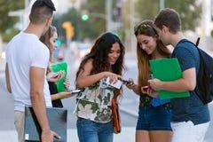 Eine Gruppe Studenten, die Spaß mit Smartphones nach Klasse haben Lizenzfreies Stockfoto