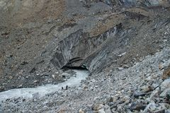 Eine Gruppe Touristen geht entlang einen kalten Gebirgsfluss von einem Gletscher auf Berg Ushba in der Svaneti-Region stockbild
