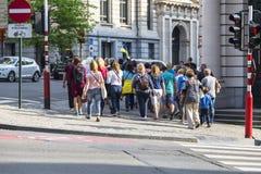 Eine Gruppe Touristen und ein F?hrer gehen durch die Stra?en von Br?ssel lizenzfreie stockbilder