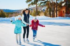 Eine Gruppe von drei Mädchen auf einer Eisbahn des Winters Rolle und Lachen lizenzfreie stockbilder