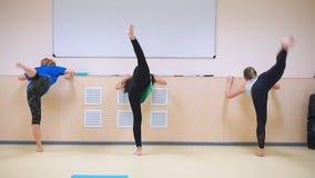 Eine Gruppe von drei Mädchen, die vertikale Schnur der Übungen ausdehnend tun stock video footage