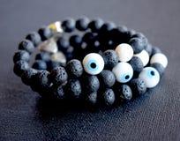 Eine Gruppe von drei perlenbesetzten Armbändern hergestellt von der schwarzen Lava auf einer schwarzen Oberfläche lizenzfreie stockbilder