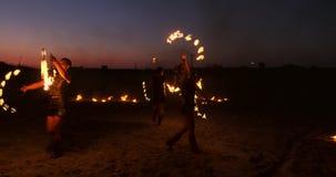 Eine Gruppe von Männern und von Frauenfeuershow nachts auf dem Sand vor dem hintergrund des Feuers und der Turmkrane stock video footage