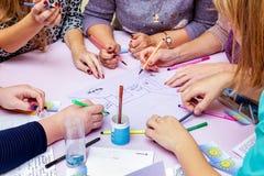 Eine Gruppe von Personen arbeitet an einem Gemeinschaftsprojekt Ausführung einer Skizze stockfotografie