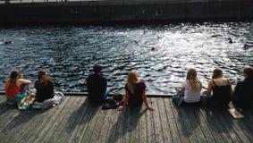 Eine Gruppe von Personen, die heraus auf der Ufergegend in Kopenhagen und den Blicken an den überschreitenen Schwimmern sitzt Lizenzfreie Stockfotografie