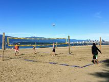 Eine Gruppe von Personen, die Strandvolleyball an einem sch?nen sonnigen Tag entlang den sandigen Str?nden von spanischen Banken, stockfotos